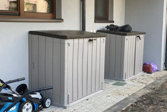 Dwie szafy ogrodowe pod ścianą budynku